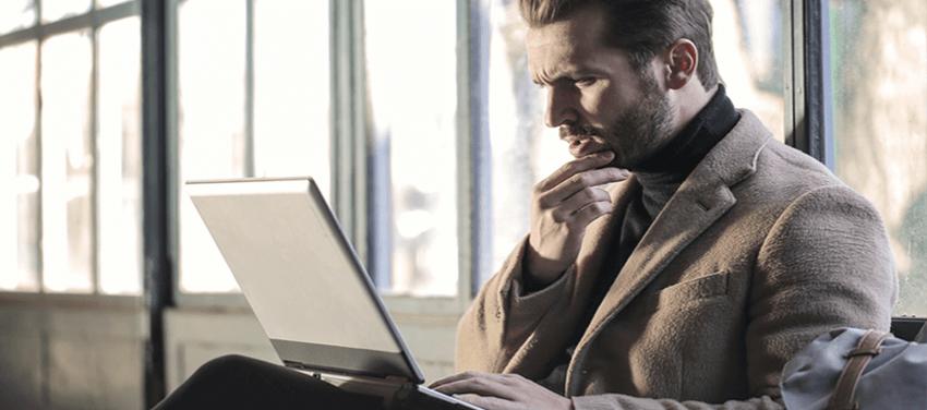man thingking facing his laptop