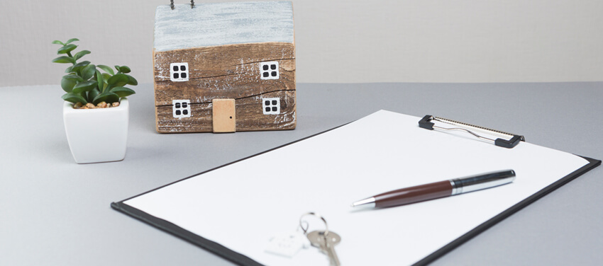 A model house and keys with clipboard grey surface